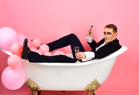 I am celebrating. Mime actor enjoy bathing in bath tub. Bathing and relaxing. Mime man has celebration party with food and drink. Comedian actor celebrate holidays. Happy bubble bath day.