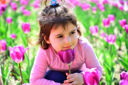 face and skincare. allergy to flower. Summer girl fashion. Happy childhood. Little girl in sunny spring. Small child. Natural beauty. Childrens day. Springtime tulips. weather forecast. In great mood. Stock Photo