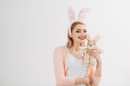 Egg hunt. Easter eggs as traditional food. Spring holiday. Girl with hare toy. Woman in rabbit bunny ears. happy woman in bunny ears with toy. Happy easter. Easter is coming, copy space.