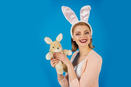 Woman in rabbit bunny ears. Egg hunt. Easter eggs as traditional food. Spring holiday. Girl with hare toy. happy woman in bunny ears with toy. Happy easter. copy space. Look what i got.