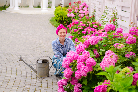 happy woman gardener with flowers. woman care of flowers in garden or greenhouse. gardener is happy for results. gardening is my passion. everything for your gardening needs. soils and fertilizers Foto de archivo - 116280567