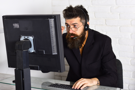 Remaining polite and reasonable. Bearded company representative at computer. Call center operator. Bearded man working in office. Man with long beard and headphones. Responding calls from customers. Фото со стока