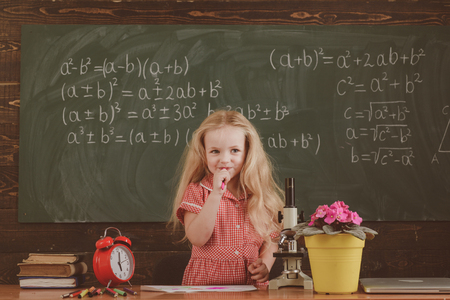 Little girl think of mathematical problem in classroom. Schoolchild solve problem in school.