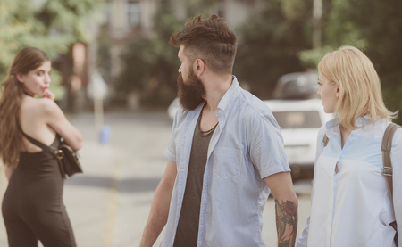 Relationship problem. Man cheating his wife or girlfriend. Bearded man looking at other girl. Hipster choosing between two women. Betrayal and infidelity. Unfaithful love. Love triangle and threesome.