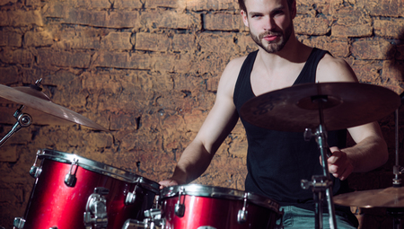 Heartbeat of the band. Man drummer playing musical instrument. Handsome man play percussion instrument. Rock concert or rehearsal in music club. Enjoying instrumental music. Rock star or rocker. Stockfoto