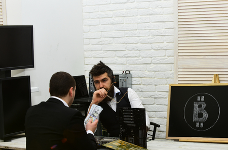 Can I pay in cash. Customer hold cash money. Bearded man with bitcoin symbol on board. Company manager and man have business meeting. Businessmen at office desk. Accepting bitcoin payments.