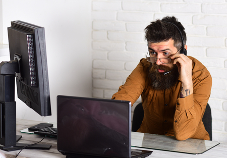 Receiving customer complaints. Man with long beard and headphones. Call center operator. Bearded man working in office. Bearded company representative with laptop. Responding the calls from customers. Stockfoto