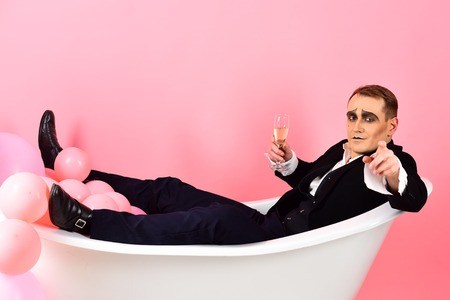 Will you join me. Mime actor enjoy bathing in bath tub. Bathing and relaxing. Mime man has celebration party with champagne. Comedian actor celebrate holidays. Happy bubble bath day.