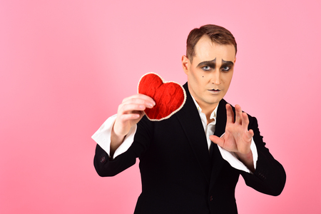 Love confession on valentines day. Theatre actor pantomime falling in love. Mime actor with love symbol. Mime man hold red heart for valentines day. An artistic expression.