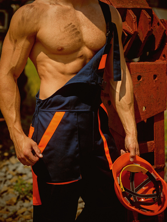 Muscular concept. Muscular body in working uniform. Muscular activity. Muscular strength and power