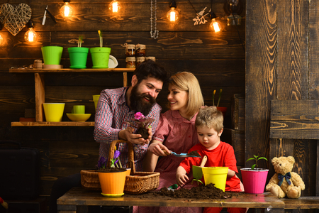 Flower care watering. Soil fertilizers. happy gardeners with spring flowers. woman, man and little boy child love nature. Family day. Greenhouse. Father and son with mother. Home day Standard-Bild - 117183528