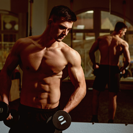 Sportsman, athlete with muscles looks attractive. Man with torso, muscular macho and his reflexion in mirror background.Man with nude torso in gym enjoy his sporty lifestyle. Sport and gym concept. Stock Photo