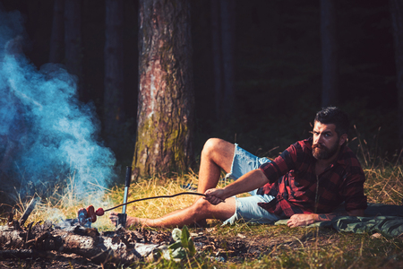 Bearded man cook food on bonfire. Hipster with beard roast sausage on fire. Man in plaid shirt relax on nature. Tourist enjoy camping. Summer vacation concept. Camping and cooking food, vintage