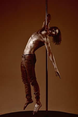 Muscular man with silver body art dancing on pylon. Athletic man make acrobatic elements on pylon. Strong dancer workout on pole. Freedom. Sexy macho with metal skin. Pole dance sport.