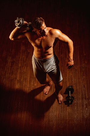 Sculpt a better body right now. Strong worker with six pack abs. Muscular man have workout in gym. Fitness and muscle training. Man exercises with dumbbell weights. Worker man with fit muscular body