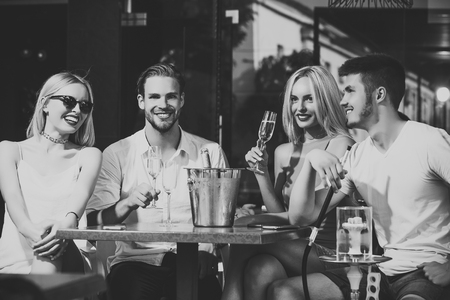 Happy friends vapor hookah and drink alcohol in bar lounge Stock Photo