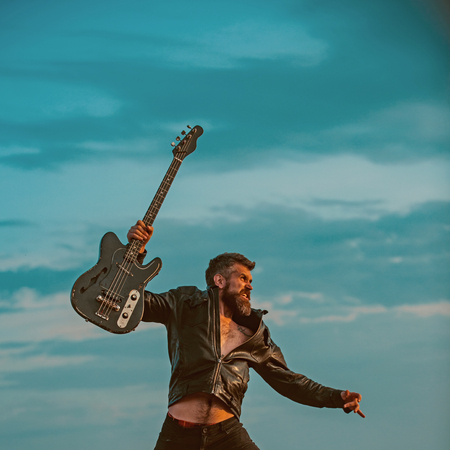 I love my guitar. Bearded man jump with guitar on blue sky. Hipster guitarist with beard on excited face fly in clouds. Feeling free and happy. Like rock star. Music is so much fun Imagens