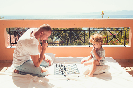 father with son on balcony play chess. Child play chess with father. Love and trust as family values. Family travel with kid on fathers day. Summer vacation of happy family