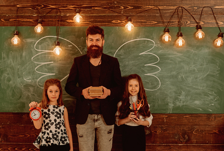 Teacher and girls pupils in classroom, chalkboard on background. Children and teacher with drawn by chalk wings. Man with beard and schoolgirls with school attributes. Favourite teacher concept.