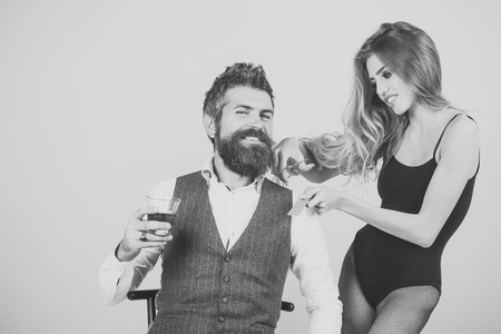 Bearded man drink whiskey, sexy woman with long curly hair.