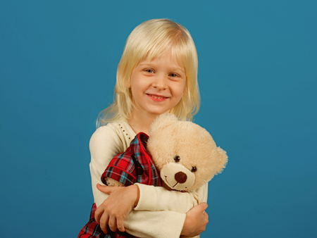 Cuddly toy. Small kid happy smiling. Happy childhood. My favorite childhood toy. Little girl with teddy bear. Small girl hold toy bear. Little child with soft toy Stock Photo