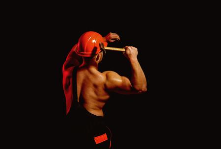 Already under construction. Construction worker hammer a nail. Muscular man builder at work under construction. Man work with hammer. Hard worker use muscular strength Фото со стока