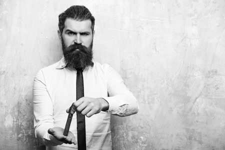 hipster or bearded man on angry face smoking cigar