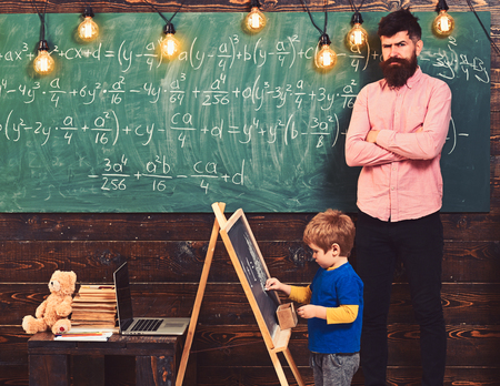 Strict math teacher checking pupil s work. Blond schoolboy solving equation at chalkboard. Preschool education concept