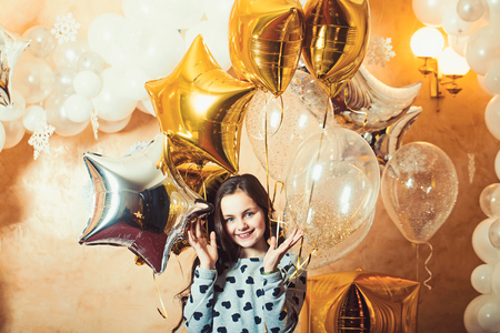 Little girl smile with golden silver star balloons, christmas. Happy child celebrate new year and xmas holidays. New year eve celebration. Party decor and design for birthday and anniversary