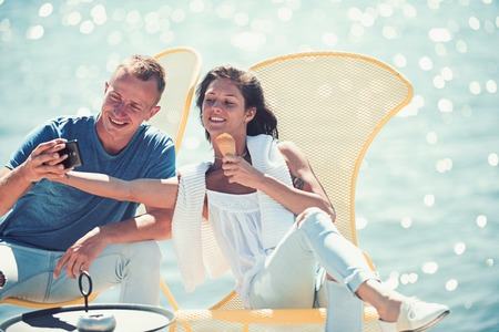 happy couple of girl and man make selfie on phone and eating ice cream at cafe. Couple in love relax at sea resort. Family and valentines day. Summer holidays and travel vacation. Love relations. Banco de Imagens