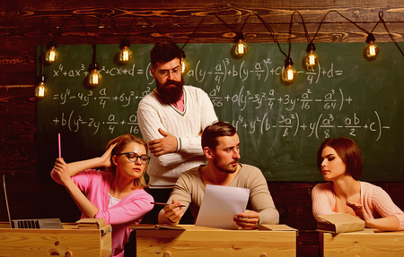Students, group mates speaking, asking for advice or cheating while teacher watching them. Bearded teacher, lecturer, professor watching students during test, exam, lesson. College education concept
