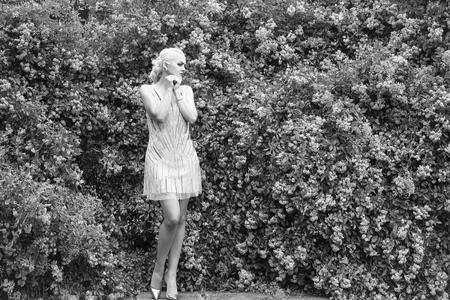 Pretty woman near rose bush