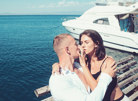 Sexy woman and man at sea bay. Family and valentines day. Love relations of kissing couple enjoying summer day. Summer holidays and travel vacation. Couple in love relax at yacht for marine travel