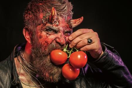 Halloween hipster devil hold red vitamin fruit