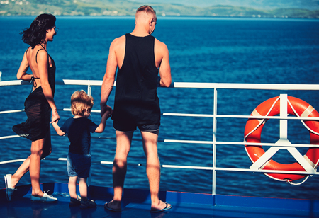 Family travel with kid on mothers or fathers day. Mother and father with son look at sea on beach. Summer vacation of happy family. Child with father and mother. Love and trust as family values. Banco de Imagens