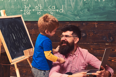 Smiling daddy teaching his son new skills. Father and son looking at each other with love. Standing kid hugging his sitting dad. Home education concept Imagens - 117188775