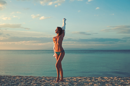 sundown woman with naked body near sea or ocean water. sundown or sunrise on summer vacation.