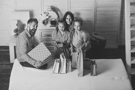 Man, woman and adorable children with gifts at home