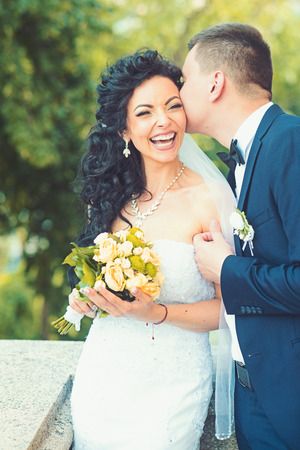 Groom kiss happy bride with bouquet. Woman and man smile on wedding day. Wedding couple in love. Newlywed couple on summer outdoor. Marriage concept. love and family