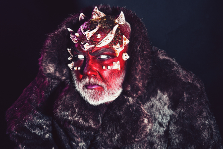 Senior man with white beard dressed like monster. Alien, demon, sorcerer makeup. Evil concept. Demon with red face on black background, close up. Man with thorns or warts in fur coat. Stock Photo
