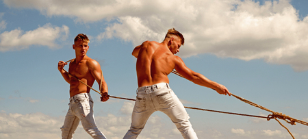 A strong team. Athletic twins with fit sexy body. Sport exercises for building strength and power. Strong men pull ropes. Twins men use muscular hand strength