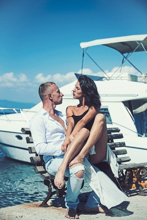 Sexy woman and man at sea bay. Family and valentines day. Love relations of couple enjoying summer day together. Summer holidays and travel vacation. Couple in love relax at yacht for marine travel