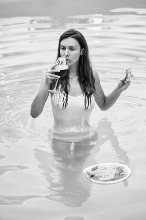girl with watermelon and wine in pool