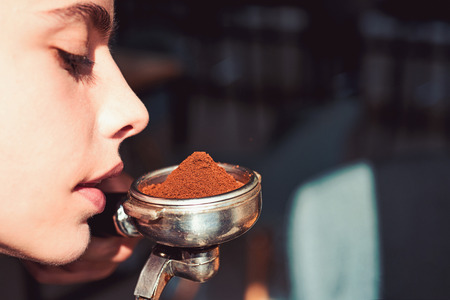 The best smell in the whole wide world. Woman barista hold portafilter in hand. Woman sniff the smell of fresh ground coffee. Barista brew espresso coffee drink. Brewing coffee device