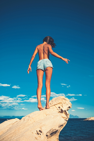 sexy woman in jeans shorts on blue sky background. Girl sunbathing topless on stone. Summer vacation and travel to ocean. Maldives or Miami beach. Sexy woman on Caribbean sea in Bahamas