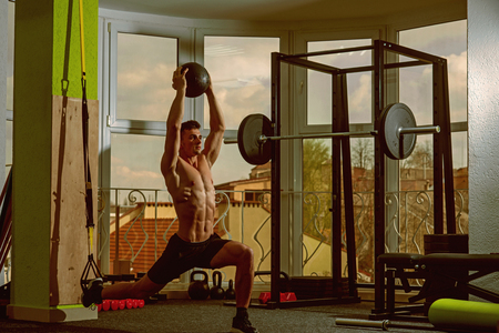Sport and gym concept. Sportsman, athlete , muscular macho does exercise with trx loops and medicine ball, window on background. Man with nude torso in gym enjoy training, trx.