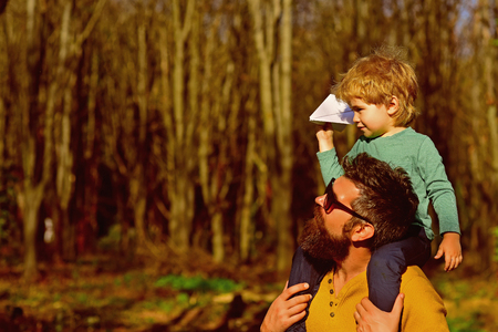 Father hold little son on shoulders with love. Loving father give child piggyback in park, love concept. Friends come and go, but family is always there