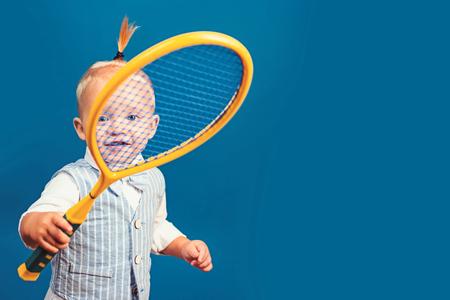 Śliczny i energiczny. Mały miłośnik sportu. Urocze małe dziecko z rakietą tenisową. Aktywne szczęśliwe dziecko. Mały tenisista. Ciesząc się moim ulubionym sportem, kopiując przestrzeń