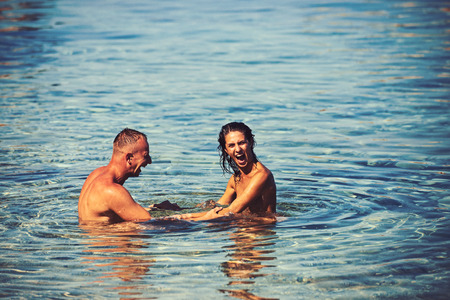 Love relations of naked couple in sea water. Sexy woman and man swim. Family and valentines day concept. Couple in love with sexy body relax on beach. Summer holidays and travel on vacation.