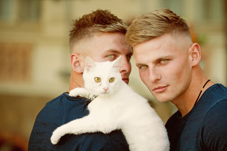 Soft and warm embrace. Muscular men with cute cat. Happy cat owners on walk with pet. Happy twins with muscular look. Cat is a part of their family Stock Photo